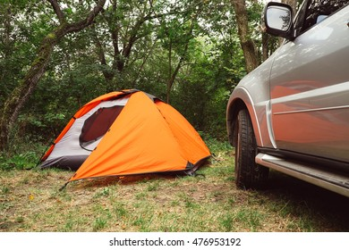 Tourist tents and SUV car in green forest at campsite. Camping place in the meadow in nature park in summer. Adventure travel active lifestyle freedom outdoors. Family time holidays.