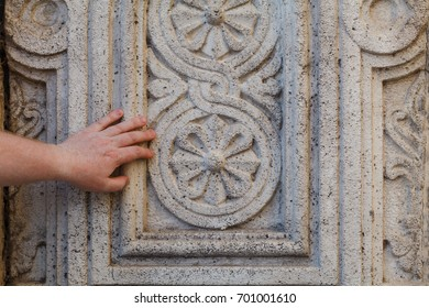Tourist touching ancient carved wall