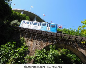 Tourist train on funicular railway on stony bridge in european city of Locarno in Switzerland above lake Maggiore in canton Ticino with clear blue sky in 2017 warm sunny summer day on July.