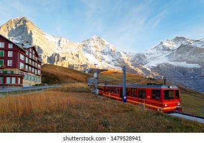 A tourist train traveling from Jungfraujoch (top of Europe) to Kleine Scheidegg & a hotel standing on a grassy hillside with Eiger, Monch & Jungfrau under sunset sky, in Bernese Oberland, Switzerland