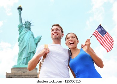 Tourist travel couple at Statue of Liberty, New York City, USA. Multiracial tourist couple on summer vacation holidays. Asian woman holding American flag smiling happy.
