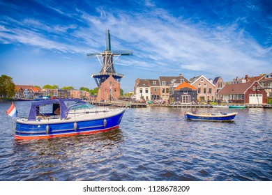 Tourist Travel Destinations. Attractive View of Harlem Sight With De Adriaan Windmill on Spaarne River On The Background At Noon.Horizontal Image Composition
