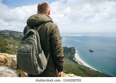 A tourist or traveler with a backpack is standing on top of a hill and admiring the beautiful view of the ocean or the sea. Walking or hiking
