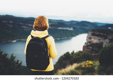 tourist traveler with backpack standing on green top on mountain, hiker view from back looking on hills and mountain river lake, girl enjoying nature panoramic landscape in trip, relax holiday concept