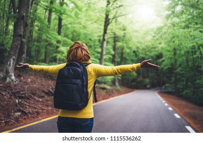 tourist traveler with backpack standing with raised hands, girl hiker view from back looking into road at forest with arms outstretched and enjoying the breath of fresh clean air in trip, relax