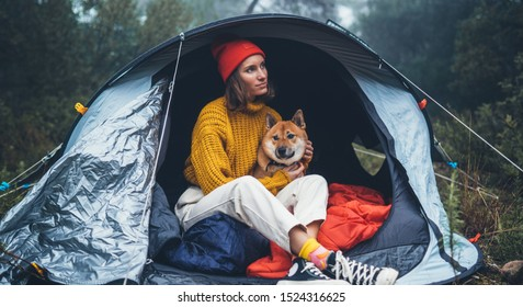 tourist traveler in camp tent hugging red shiba inu on background foggy rain forest, hiker woman with puppy dog in mist nature trip, friendship love concept, happy girl resting dog together