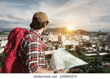 Tourist Traveler Hipster Young Man standing on the peak of natural mountain and rejoices sunset with red backpack and holding map on background valley landscape view.