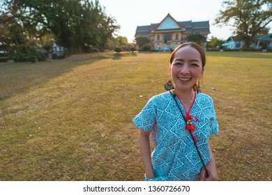 Tourist traveler in lanna uniform with Natural Scene background of Tunnel of dry Plumeria Tree or Frangipani tree with walking way at Nan province , Thailand