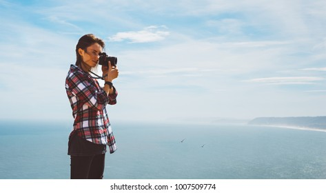 Tourist traveler photographer making pictures sea scape photo camera on background ocean, hipster girl looking on nature horizon, relax holiday, blank space blue waves view, blurred backdrop for text