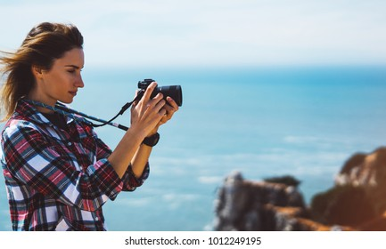 Tourist traveler photographer making pictures sea scape on photo camera on background ocean, hipster girl look on nature horizon, relax holiday, blank space blue waves view, blurred backdrop for text