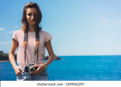 Tourist traveler photographer making pictures holding photo camera on background ocean sea scape, hipster girl looking on nature horizon, relax holiday, blank space blue waves view, backdrop for text