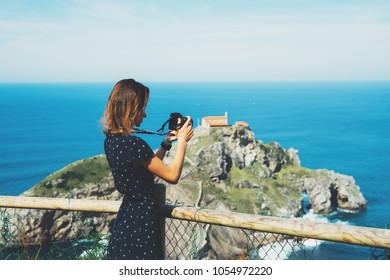 Tourist traveler photographer making pictures sea scape on photo camera on background ocean gaztelugatxe steps on Spain, hipster girl looking on nature horizon, relax holiday, blank space waves view