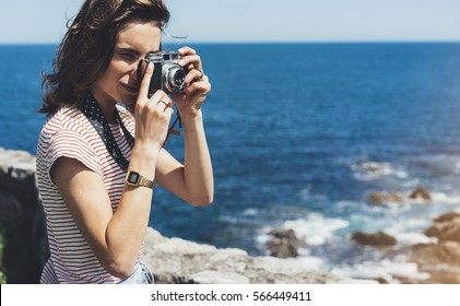 Tourist traveler photographer making pictures sea scape on vintage photo camera on background piar, hipster girl enjoying peak mountain and nature holiday, mockup ocean waves view, blurred backdrop