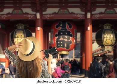 Tourist is traveling at Kaminarimon (The gate of Sensoji Temple). It has kanji written in black on a big red paper lantern means Thunder Gate. This place is a famous landmark in Asakusa ,Tokyo,Japan.