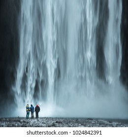 Tourist under the waterfall in Iceland, Adventure photo, edit space