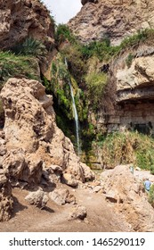 a tourist viewing the david falls on the david stream in the ein gedi park in israel showing the cliffs and tropical vegetation growing in the desert