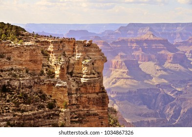 Tourist viewpoint and rockwalls of the South rim of the Grand Canyon with beautiful long sight view in the background.