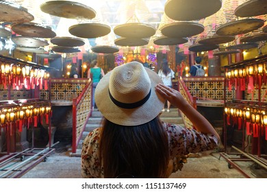 Tourist is visiting and looking beatiful  joss stick released smork decoration inside Man Mo  Chinese buddhistTemple in Hong Kong.