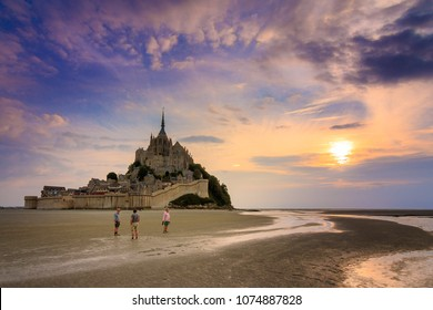 Tourist walk around historic landmark Le Mont Saint-Michel in Normandy, France, a famous UNESCO world heritage site and tourist attraction, at sunset and low tide