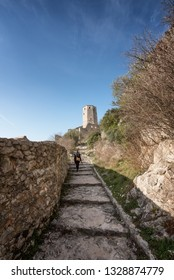A tourist walkin towards the Kula, a silo-shaped fort overlooking the Ottoman village of Pocitelj, in Bosnia and Herzegovina.