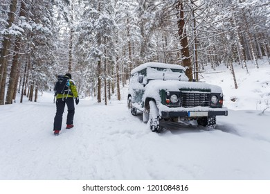 Tourist walking alone through winter forest passing off-road parked car