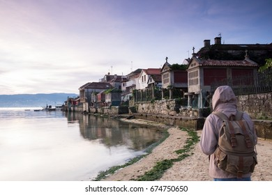 tourist walking along the seashore in the town of Combarro, Pontevedra, Galicia, Spain
