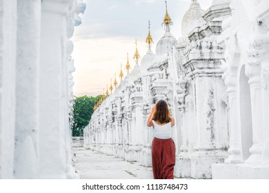 Tourist walking among of stupa in Kuthodaw Pagoda, known as the world's largest book in the evening. Kuthodaw is a Buddhist stupa, located in Mandalay, Burma (Myanmar), at the foot of Mandalay Hill.