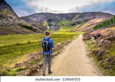 Tourist walking in the Cairngorm Mountains, south of the Grampians. Pathway around Loch Lee, Angus, Aberdeenshire, Scotland, UK.