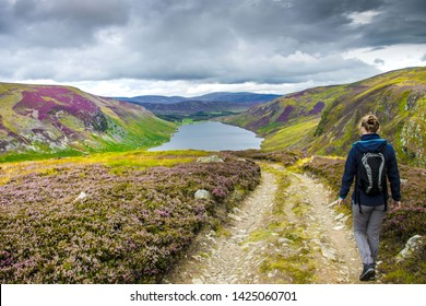 Tourist walking down from Cairn Lick to Loch Lee. Angus, Scotland, UK. Cairngorms National Park.
