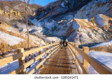 tourist walking on beach wooden bridge with backpack at Jigokudani or Hell Valley in Hokkaido, Japan. popular tourist destination to visit.