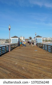 Tourist walking on the Oceanside Pier during blue summer day, Oceanside, northern San Diego County, California. Wooden pier on the western United States coastline. Famous for fisher. 03/22/2019