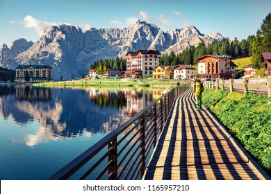 Tourist walking on the pier on Misurina lake. Sunny morning scene of Misurina resort, National Park Tre Cime di Lavaredo, Location Auronzo, Dolomiti Alps, South Tyrol, Province of Belluno, Italy, Euro