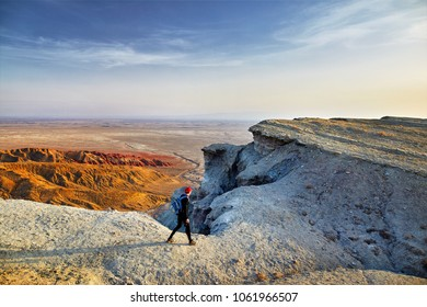 Tourist walking at the on surreal white mountains in desert park Altyn Emel in Kazakhstan