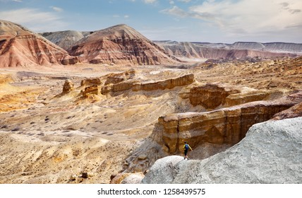Tourist walking at the trail on surreal yellow mountains in desert park Altyn Emel in Kazakhstan