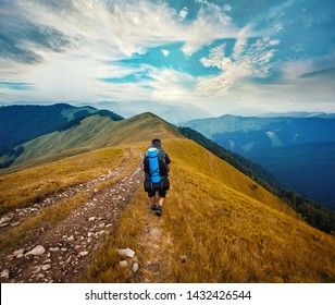 A tourist walks along a mountain meandering trail. Summer walking in mountains