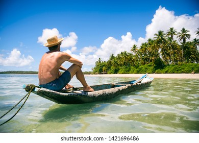 Tourist wearing a straw sun hat sitting in a rustic dugout canoe on a sunny palm-lined tropical island beach in Bahia, Brazil
