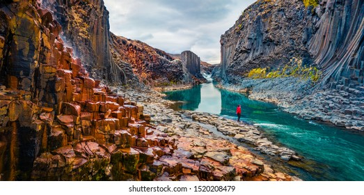 Tourist went to the bottom of canyon and admired the beauty of basalt columns. View from flying drone of Studlagil Canyon. Picturesque summer scene of Iceland. Beauty of nature concept background.