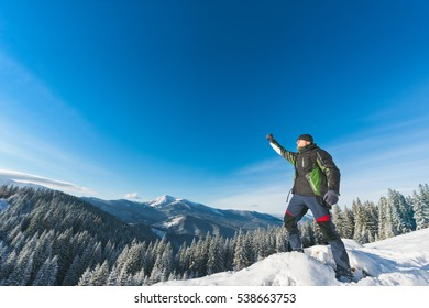 Tourist winner with a backpack standing in the snowy mountains Carpathians, Ukraine, Europe, success, good day, achieving goals