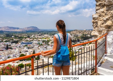Tourist woman in ancient Archangelos castle in scenic old town on Rhodes island, Dodecanese, Greece. Beautiful picturesque white houses with flowers. Famous tourist destination in South Europe