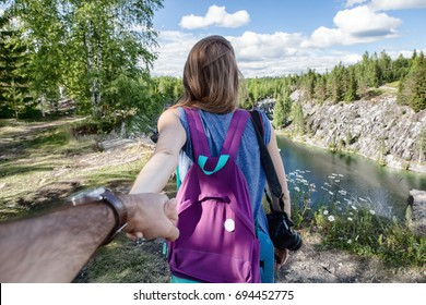 Tourist woman with backpack holding man by hand and walking down the mountain valley