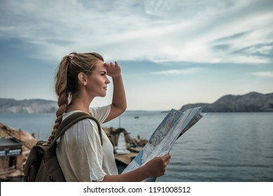 Tourist woman with backpack and map hiking and looking at sea bay view