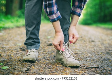 Tourist woman binds hiking boots on a forest path. Traveler wearing hiking shoes.