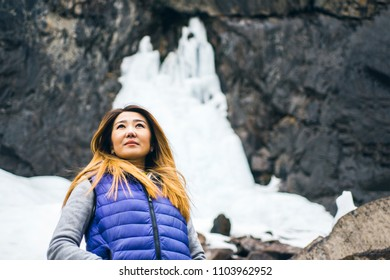 Tourist Woman in blue is looking into the distance and rocks with winter frozen waterfall on background. Copy space for text