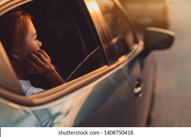 Tourist woman bored when encountering a traffic jam for over many hours during a weekend long tour and traveling with blue hatchback car and friends together on summer road trip at sunset.