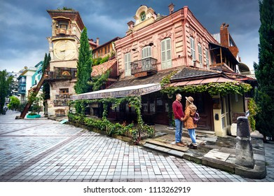 Tourist woman in brown hat and man in red shirt looking on tower of puppet museum at the street of central Tbilisi, Georgia