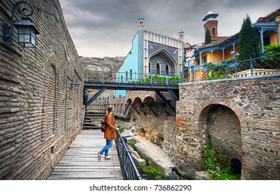 Tourist woman in brown jacket walking down the Old streets of Public Sulfuric bath district in central Tbilisi, Georgia
