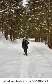 Tourist woman with camera hiking on a snowy trail in the mountains