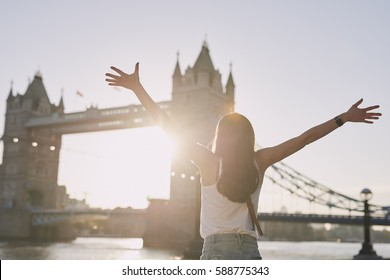 Tourist woman celebrates arms raised at Tower Bridge destination sunset in London on adventure travel vacation