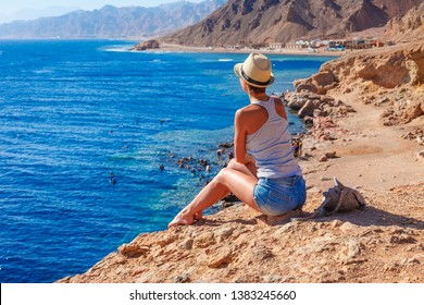 Tourist woman in Dahab near Blue Hole at the Red Sea coast. Famous travel destionation in desert. Sharm el Sheik, Dahab, Sinai Peninsula, Egypt.