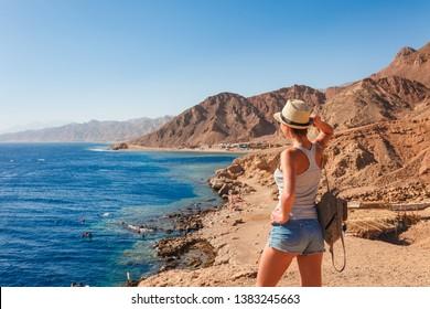 Tourist woman in Dahab near Blue Hole at the Red Sea coast. Famous travel destionation in desert. Sharm el Sheik, Dahab, Sinai Peninsula, Egypt.